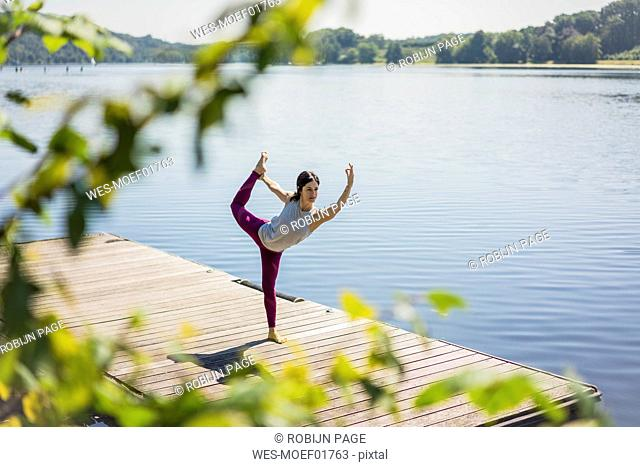 Mature woman practicing yoga in summer on a jetty at a lake