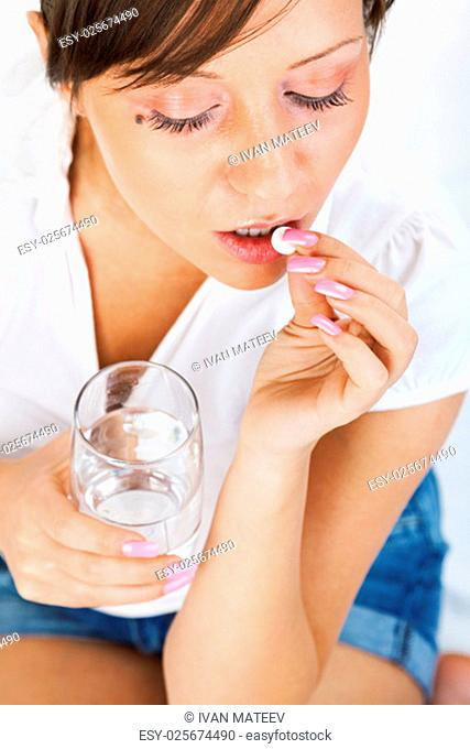 Young woman taking a pill isolated on white background