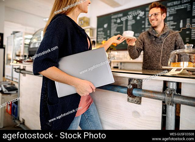 Young woman with laptop in a cafe ordering a cup of coffee
