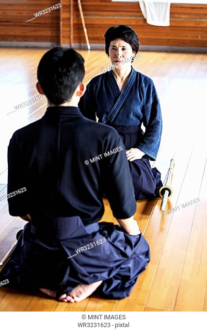 Female and male Japanese Kendo fighters kneeling opposite each other on wooden floor