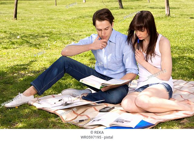 Young couple sitting on blanket with papers
