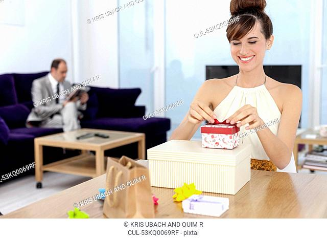 Woman opening presents at table