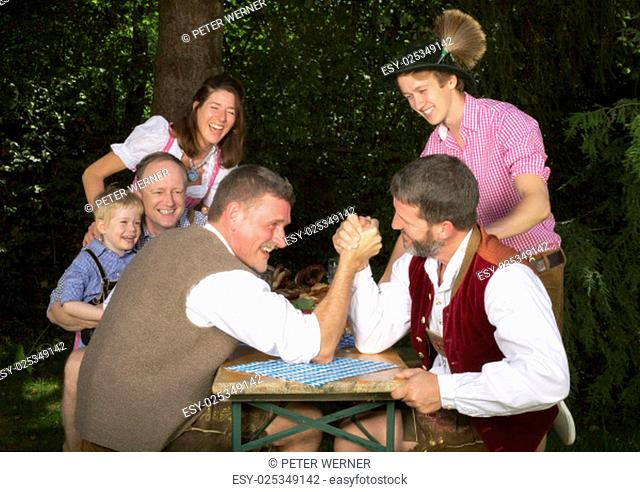 two bavarian men pressing hands while people watching