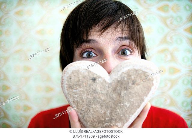 Retrato de mujer de pelo moreno y ojos verdes con corazon en las manos, amor, Portrait of brown-haired woman with green eyes with heart in her hands, love