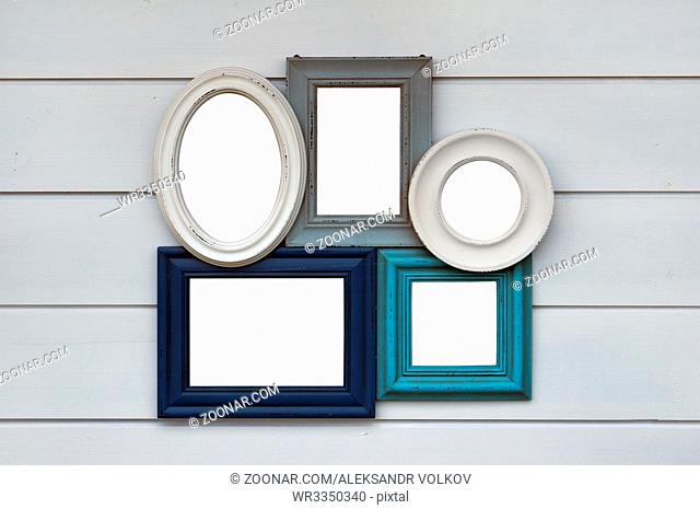 Vintage framework for pictures or photos hangs on a wooden white wall of the rural house. Paper area isolated with patch