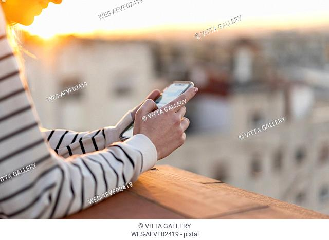 Young woman on balcony using mobile phone, partial view