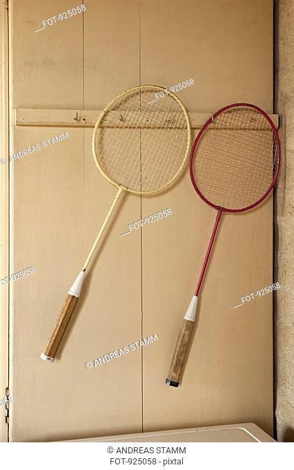Two badminton racquets hanging on a wall