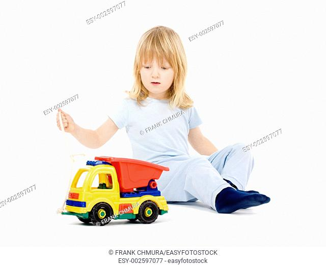 boy with long blond hair playing with a toy truck - isolated on white