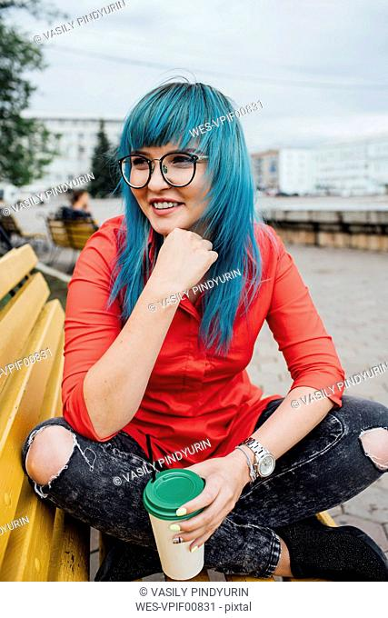 Portrait of smiling young woman with dyed blue hair sitting on a bench with beverage