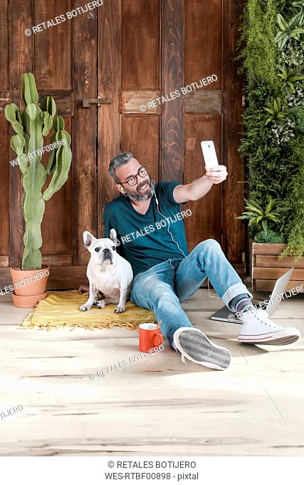 Bearded man sitting with his dog on the floor at home taking selfie with smartphone
