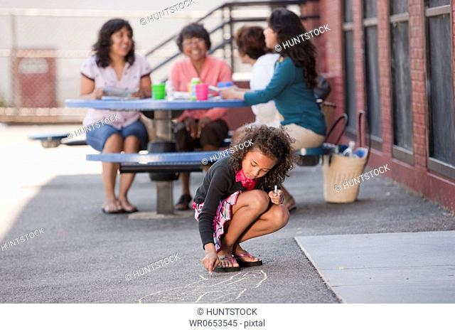 Hispanic girl drawing on the floor with her family in the background