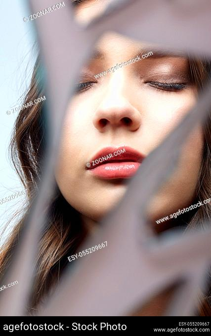 Young woman looks in a broken mirror. Portrait of beautiful female in the mirror shards. Eyes closed