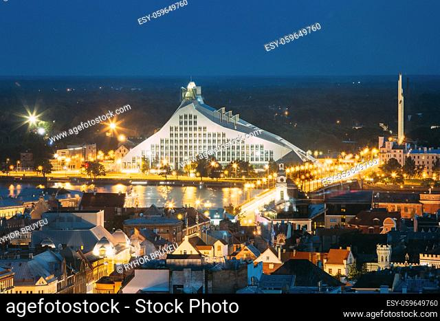 Riga, Latvia. Aerial View Of Cityscape In Summer Evening Or Night Lights Illumination. Top View Of Latvian National Library At Blue Hour