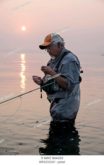 Man tying a fly on his fly fishing line while fishing for salmon and searun cutthroat trout