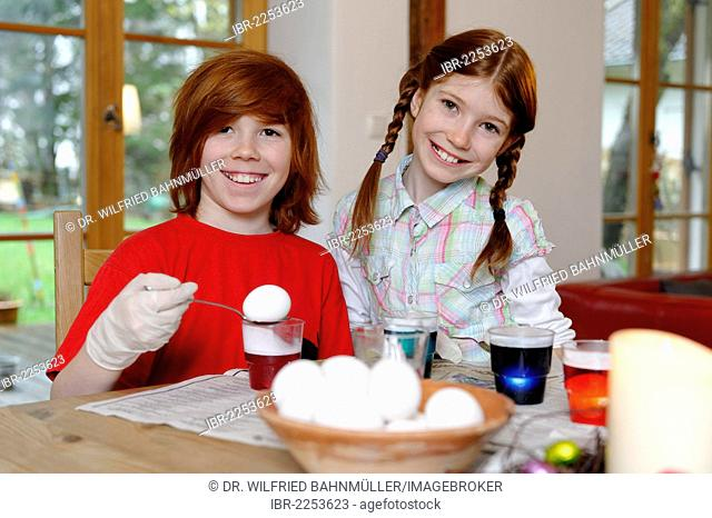 Boy and girl coloring Easter eggs, painting Easter eggs