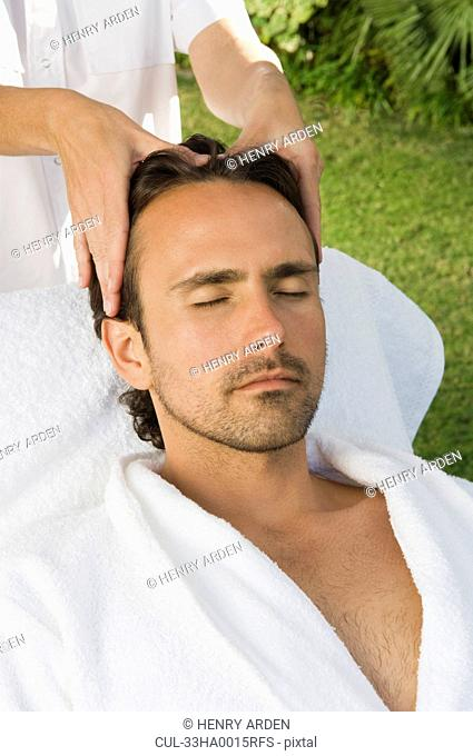 Man having scalp massage outdoors