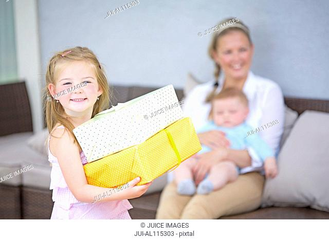 Girl holding gifts with baby boy and mother in background