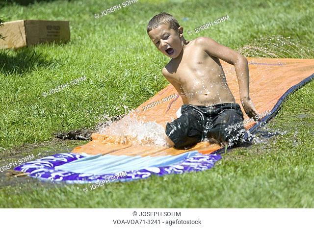 Little boy sliding on a water slide in North Platte, Nebraska on a very hot summer day