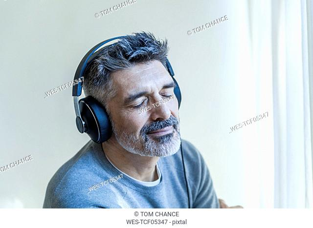 Mature man with closed eyes wearing headphones