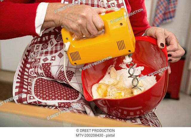 Senior woman mixing egg, butter and flour in a mixing bowl, Munich, Bavaria, Germany