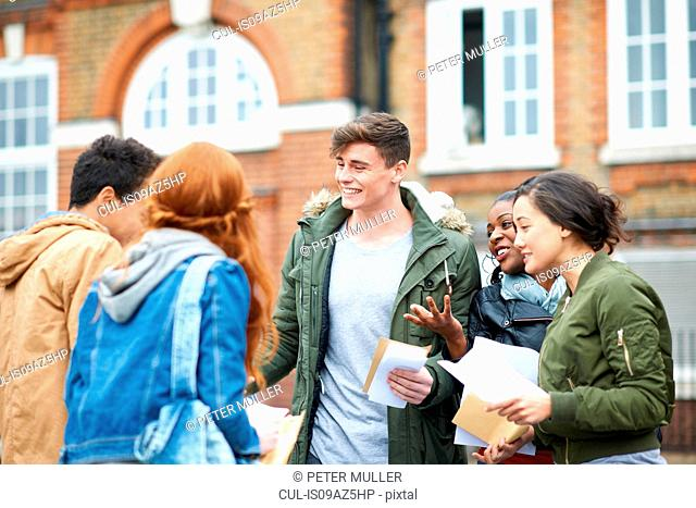 Happy young adult college students congratulating each others exam results on campus