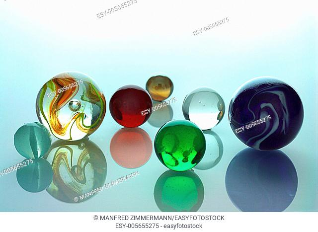 Several different colored glass balls on Spiegelflaeche