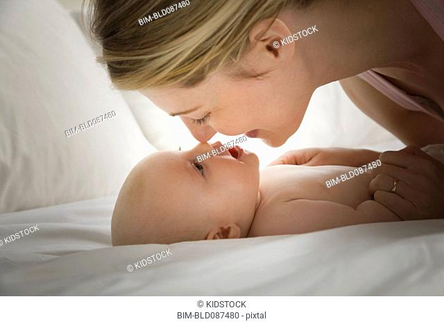 Caucasian mother rubbing noses with baby girl
