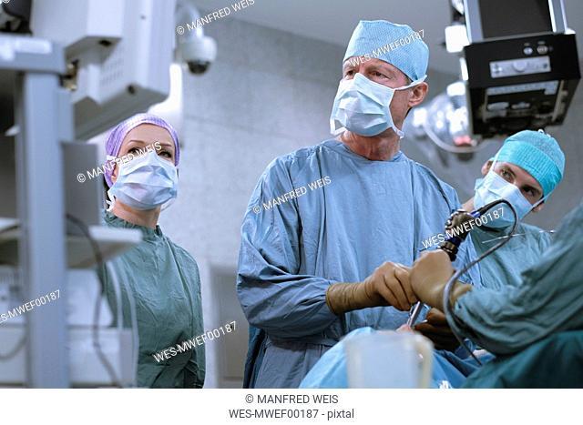 Team of neurosurgeons in scrubs during an operation