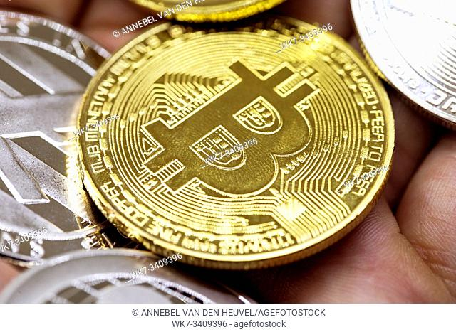 Golden Bitcoin in a man hand, Digitall symbol of a new virtual currency with black and white background
