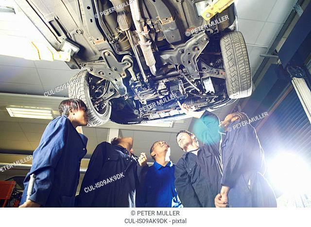 Five college students looking up from beneath car in garage workshop