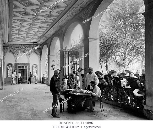 European-Mexican administrator sits in a Hacienda porch, San Luis Potosi, Mexico, c. 1890. Landless mestizo peons wait their turn for an audience with the...