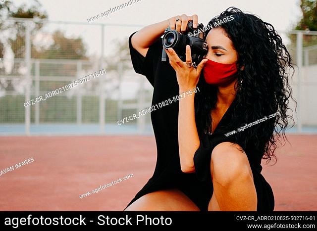 Young woman taking photo with camera wearing face mask