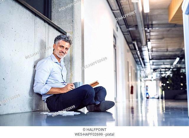Portrait of smiling mature businessman sitting on the floor