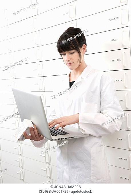 This picture shows a young caucasian woman with brown hair pharmacist as she takes and check medical products / drugs in a drawer