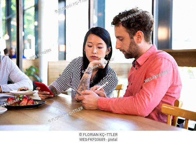Casual business people having a meeting in a cafe using cell phone