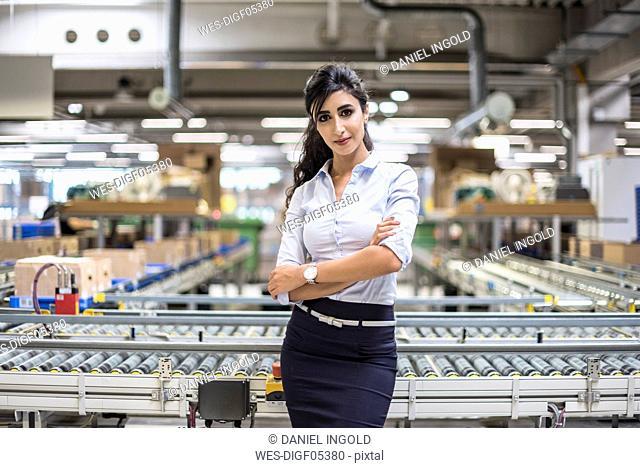 Portrait of confident woman at conveyor belt in factory