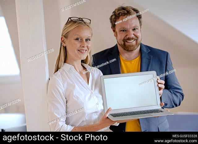 Portrait of confident businessman and businesswoman in office presenting laptop
