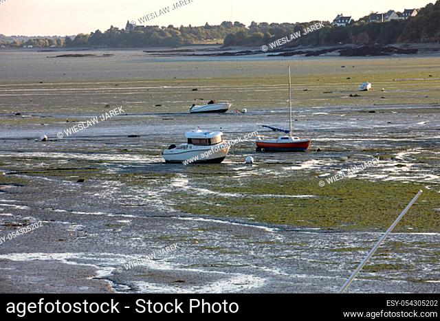 Boats on dry land at the beach at low tide in Cancale famous oysters production town, Brittany, France