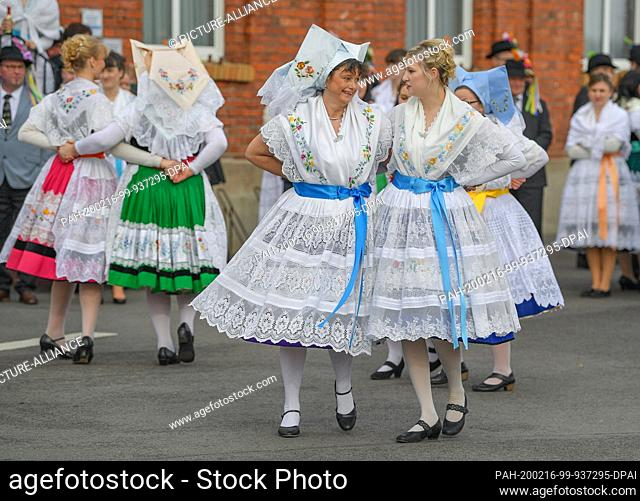 15 February 2020, Brandenburg, Neu Zauche: Women in original Sorbian-Wendish Spreewald costumes from the village of Straupitz dance on a street during the...