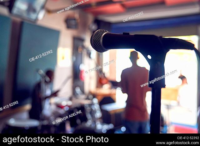 Microphone and musicians in garage recording studio