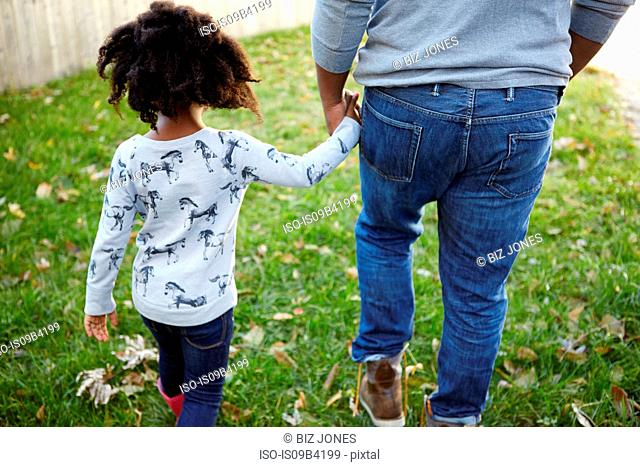 Rear view of man strolling hand in hand with daughter in garden