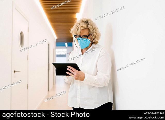 Mature dentist with protective face mask using digital tablet at clinic corridor