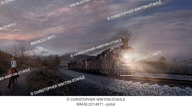 Woman on horse watching train in remote landscape