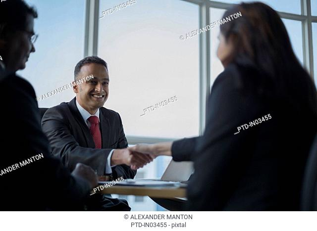 Singapore, Man looking at businessman shaking hands with woman