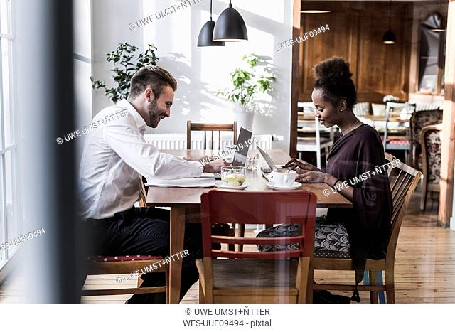 Young man and woman using laptop and tablet in a cafe