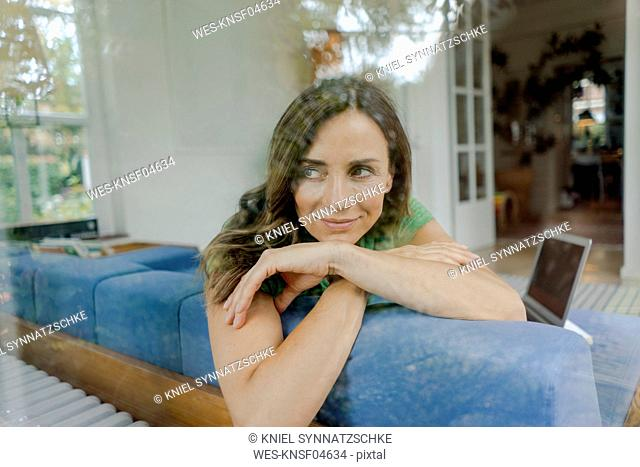 Smiling mature woman on couch at home looking sideways