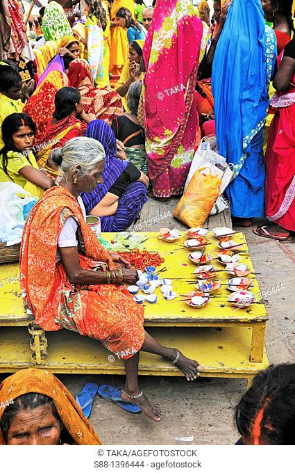 Woman sell flower with candle at main ghat