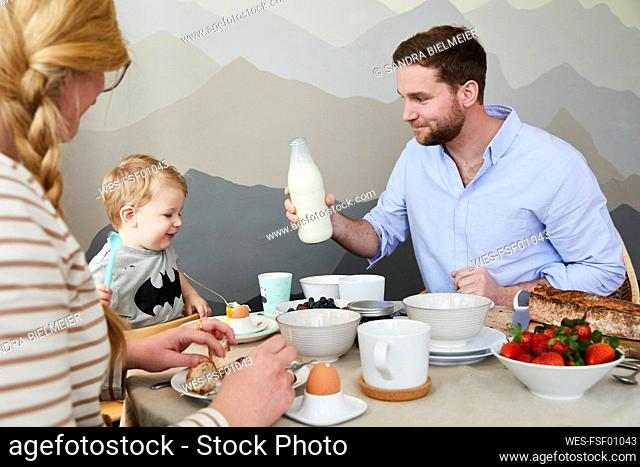 Little boy sitting at breakfast table with his parents