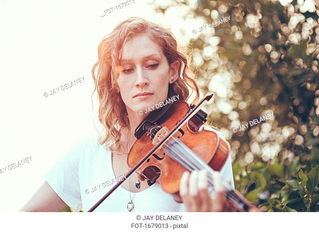 Confident beautiful woman playing violin against plants