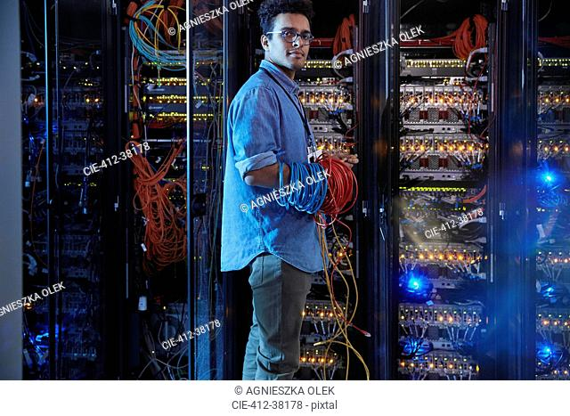 Portrait confident male IT technician holding cables in server room